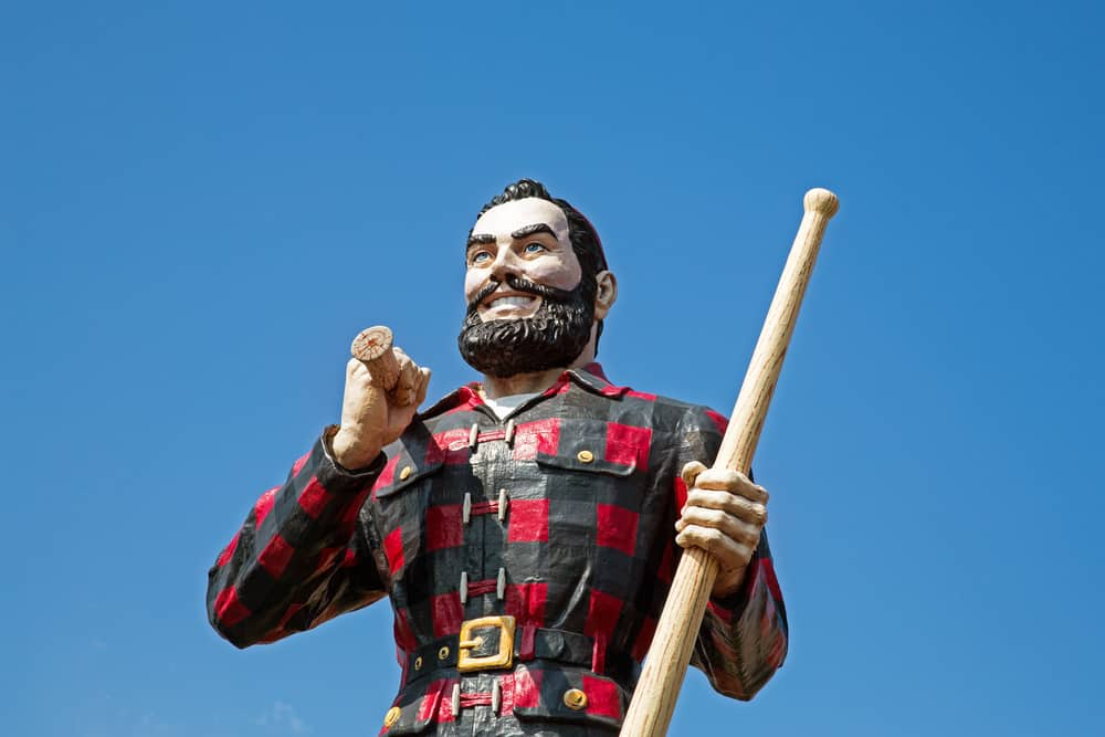 Tall statue of a man with a beard in a red and black plaid shirt.