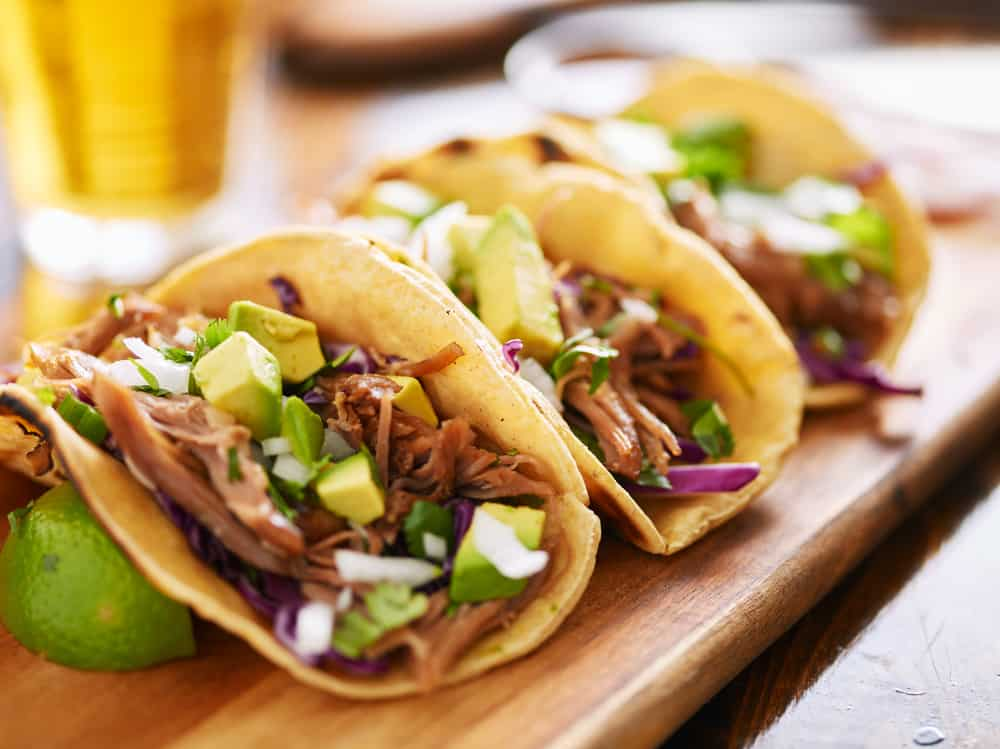 Row of tacos on a cutting board