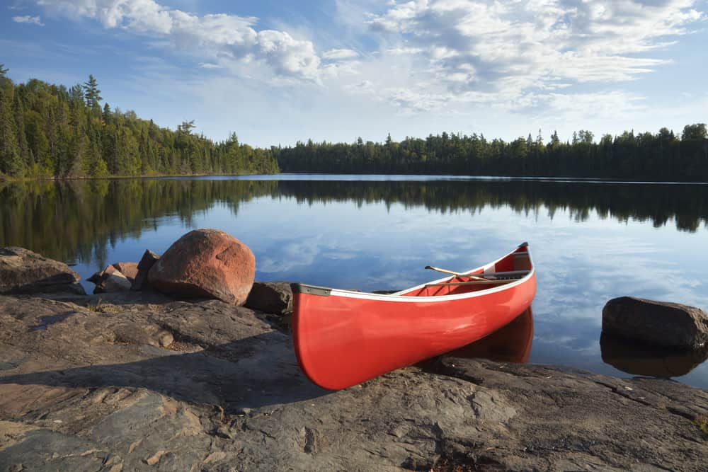 Red canoe sitting on a rock next to a lake