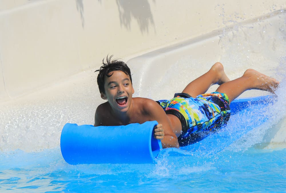 Child having fun riding on belly down a waterslide