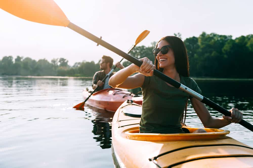 Girl smiling while in a yellow kayak