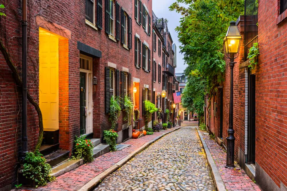 Old cobblestone walkway surrounded by red brick buildings
