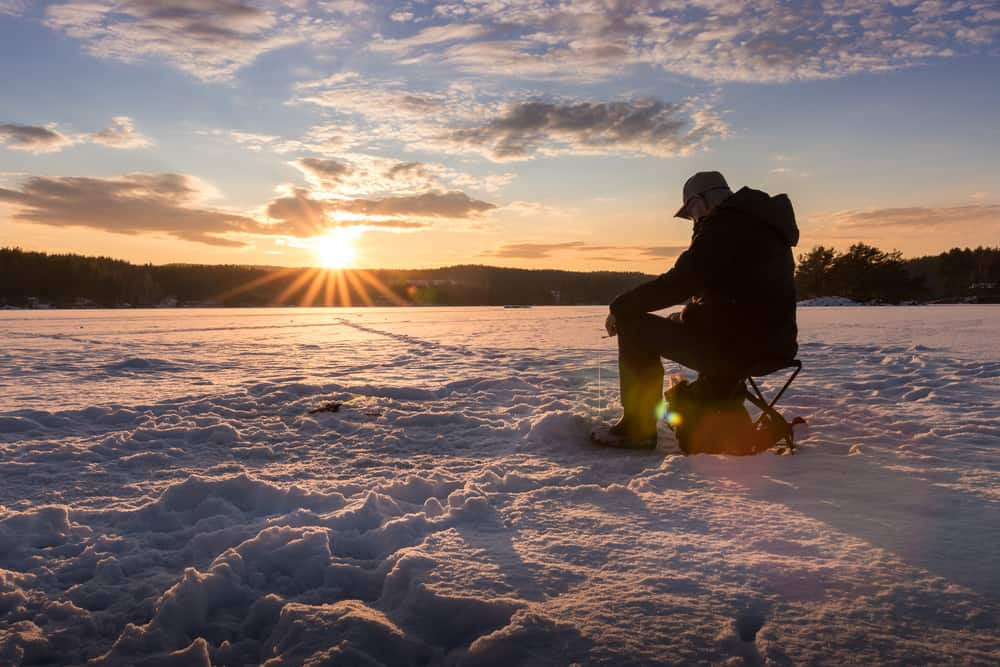 Man sitting and fishing in the winter on a lake surrounded by snow.
