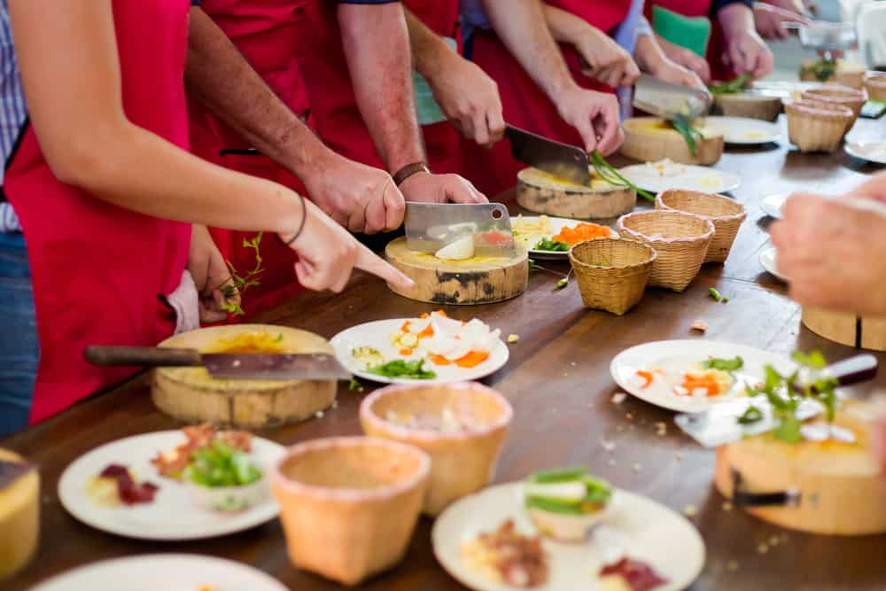 Group of people preparing food on a table