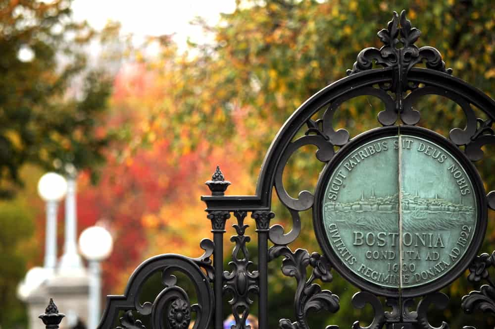 fall leaves are blurred behind a fancy gate that says Boston - quotes about boston image