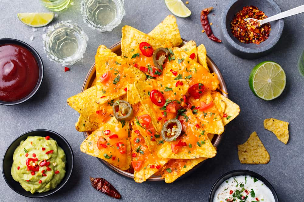 Bowl of nachos on a table with cheese, jalepenos, and guacamole