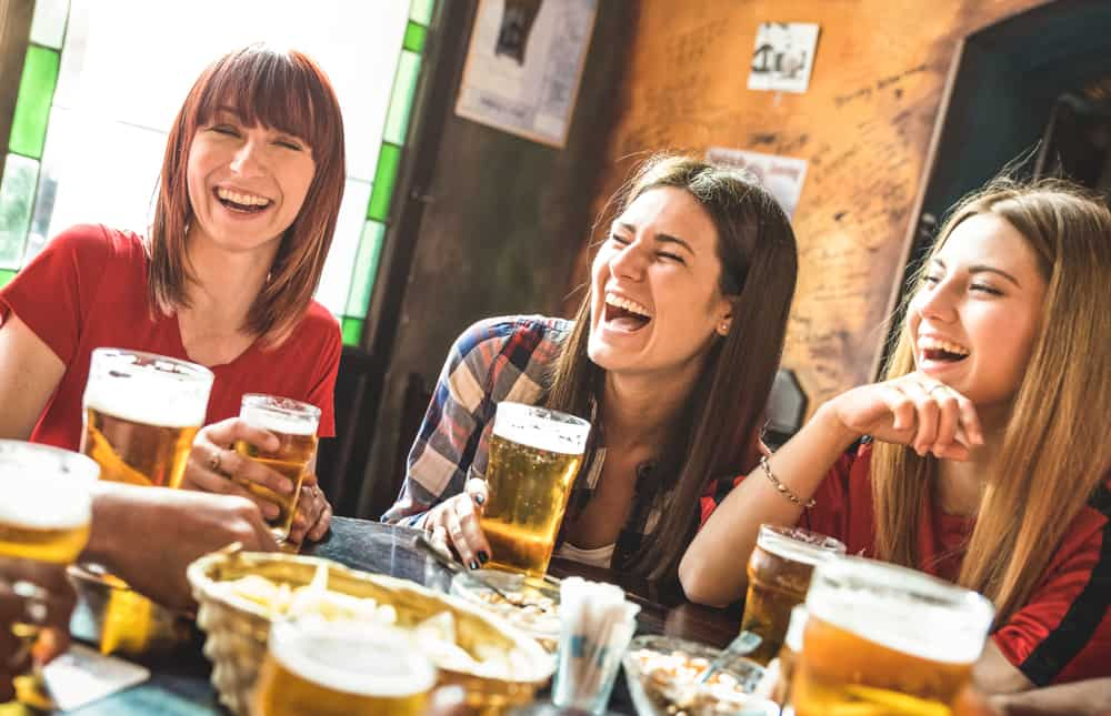 Friends laughing at a table with pints, Breweries in New England