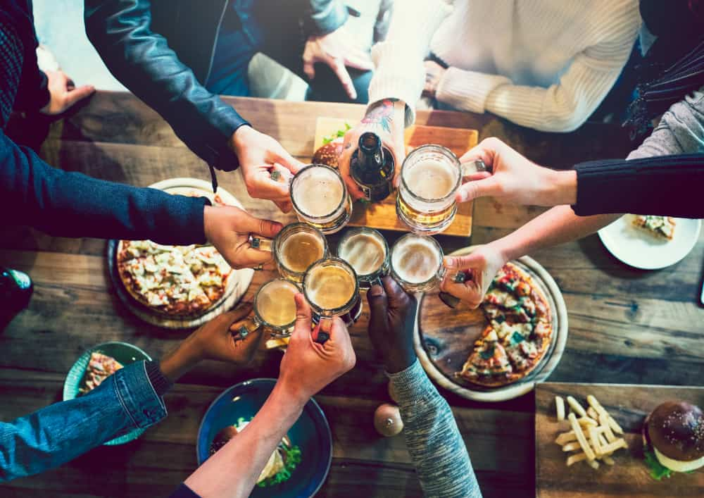 Hands holding beer at a table