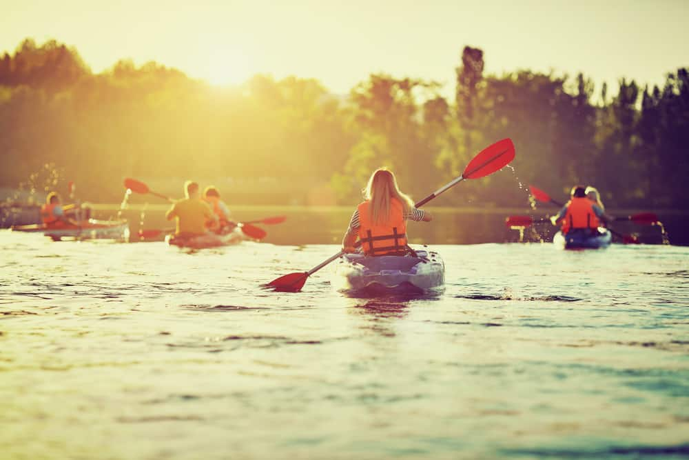 People kayaking with life vests on the water