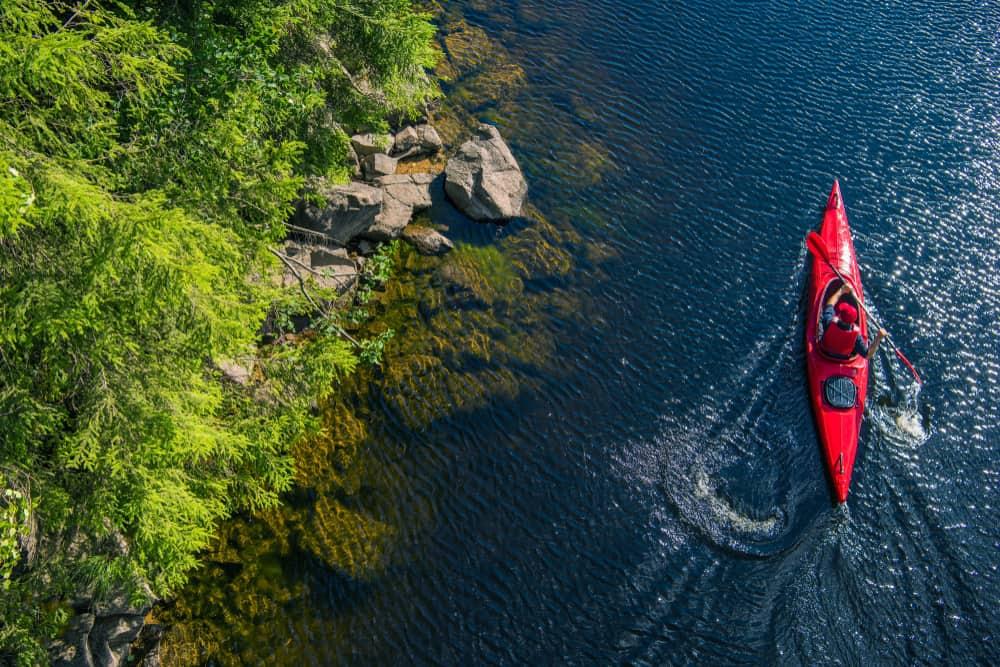 Aerial view of man kayaking in a red kayak
