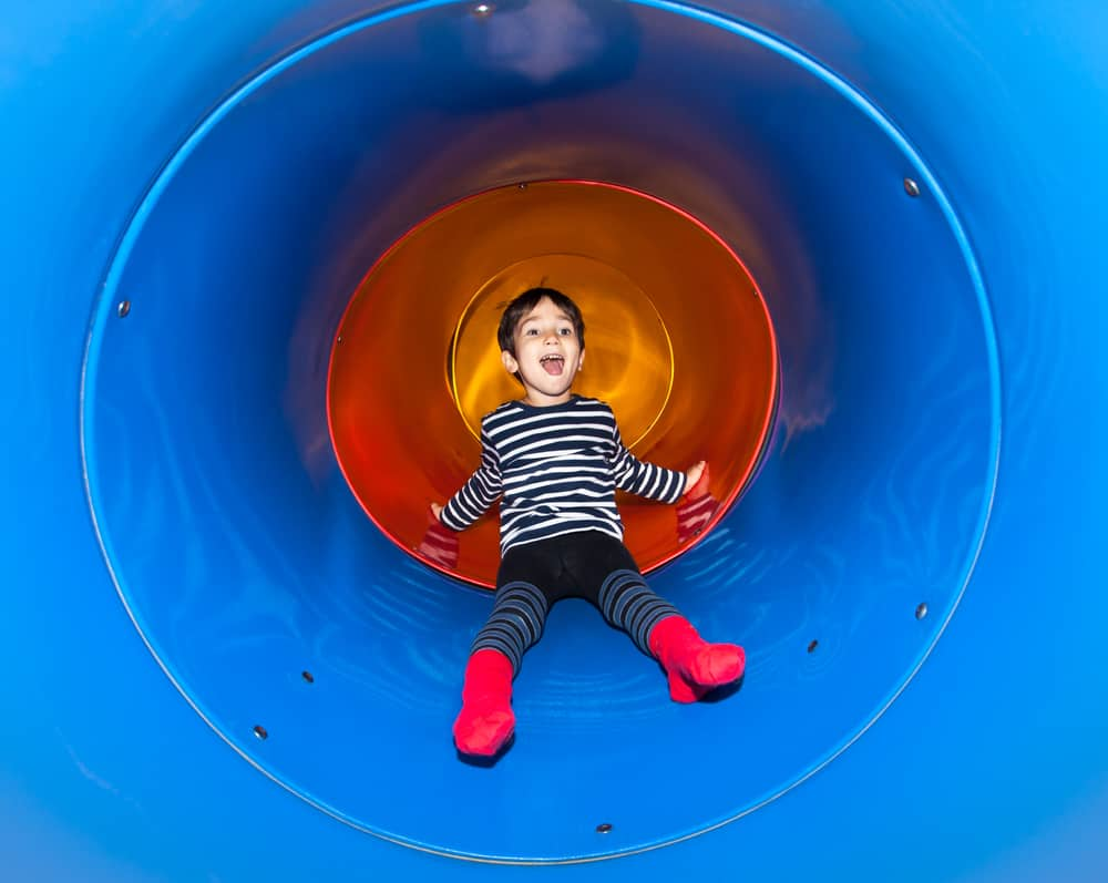 Kid having fun riding down a slide