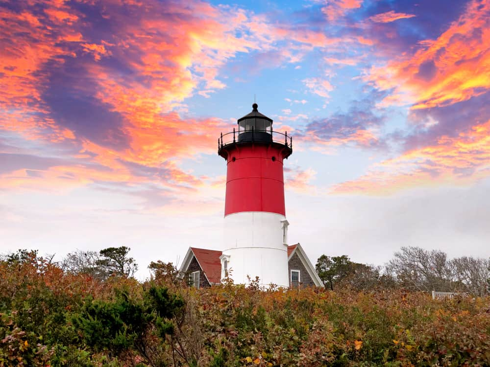 Red and white lighthouse under a sunset, cape cod in the fall