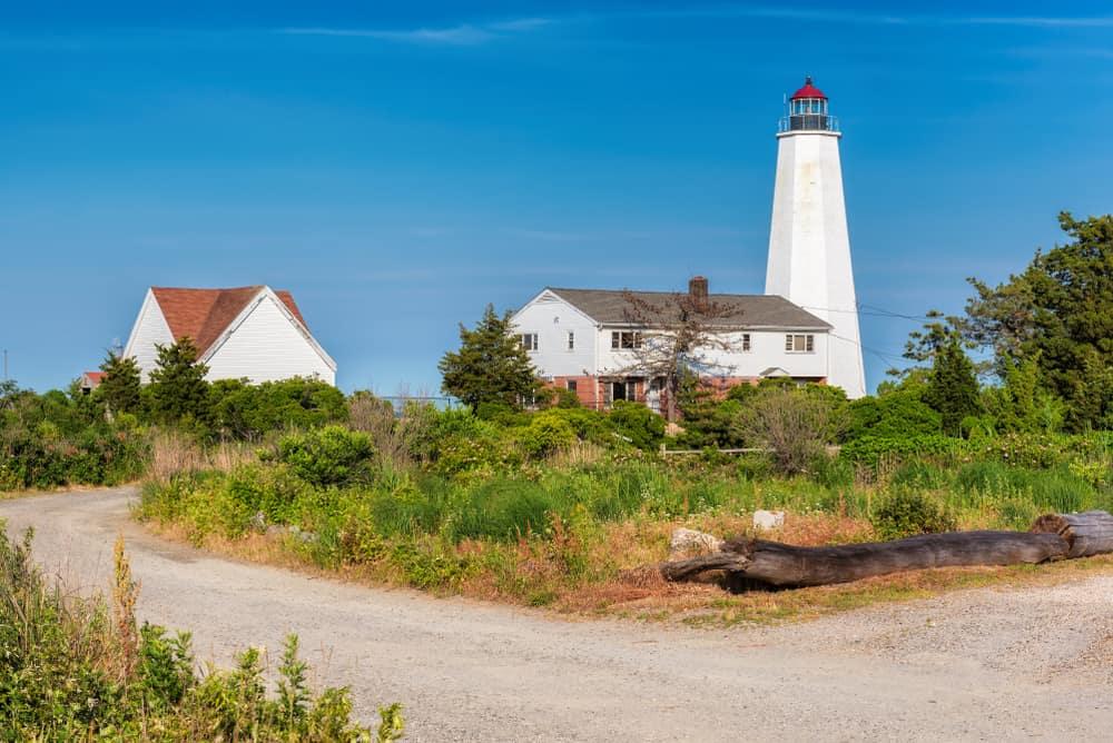 Lighthouse on the beach next to a house