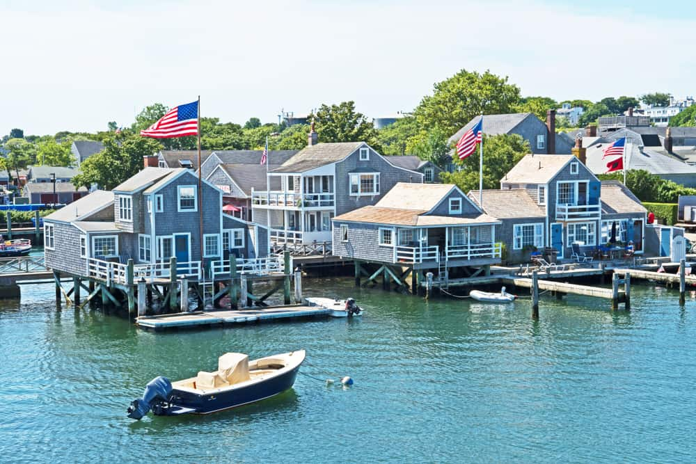Blue water with boats and piers next to houses, beach towns in new england