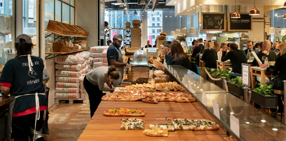 Tons of pizza on a table being ordered in Eataly