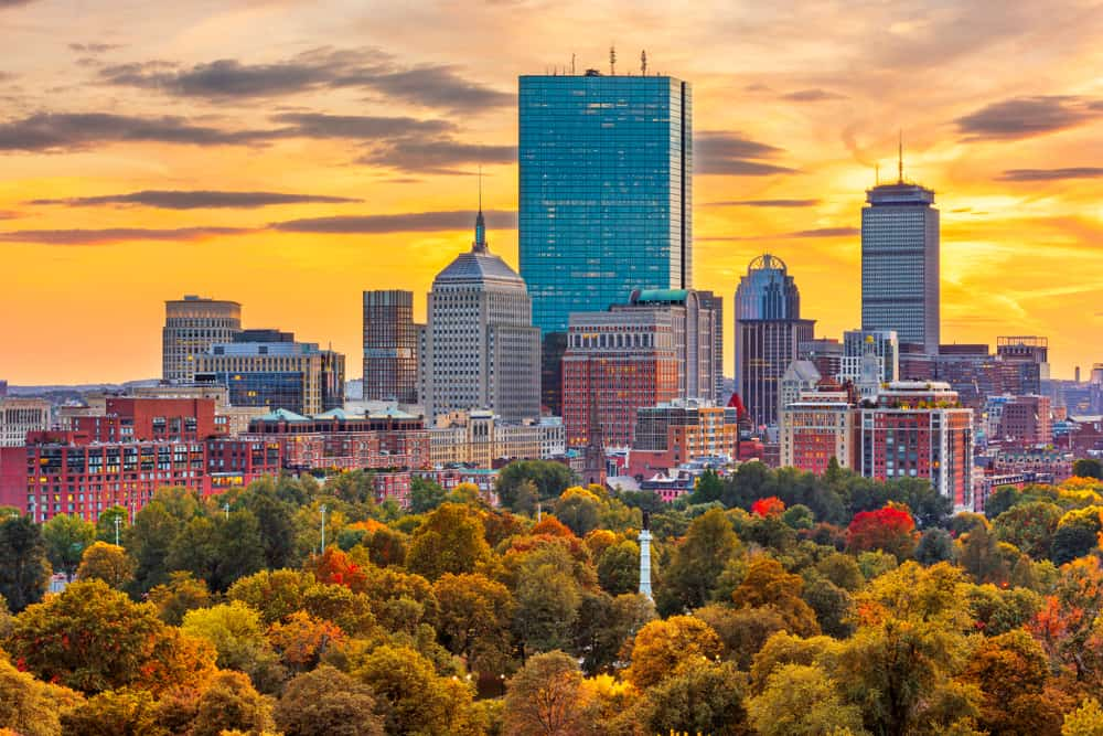 View of the boston skyline in the fall with an orange sky, fall in Boston