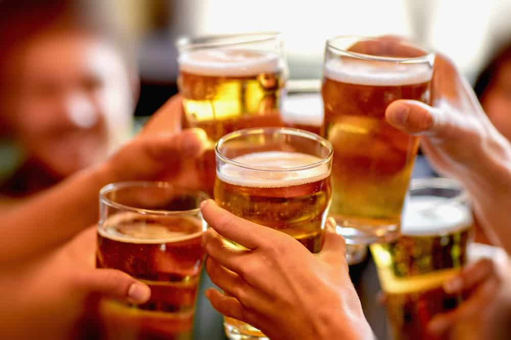 Friends clinking pints of beer