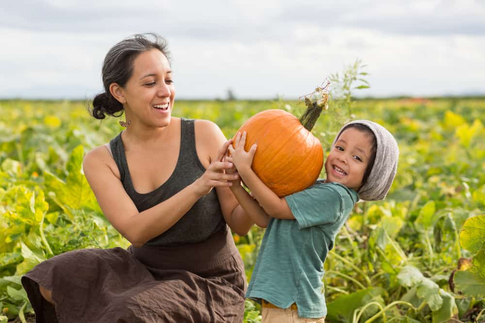 Mom and child holding a pumpkin together