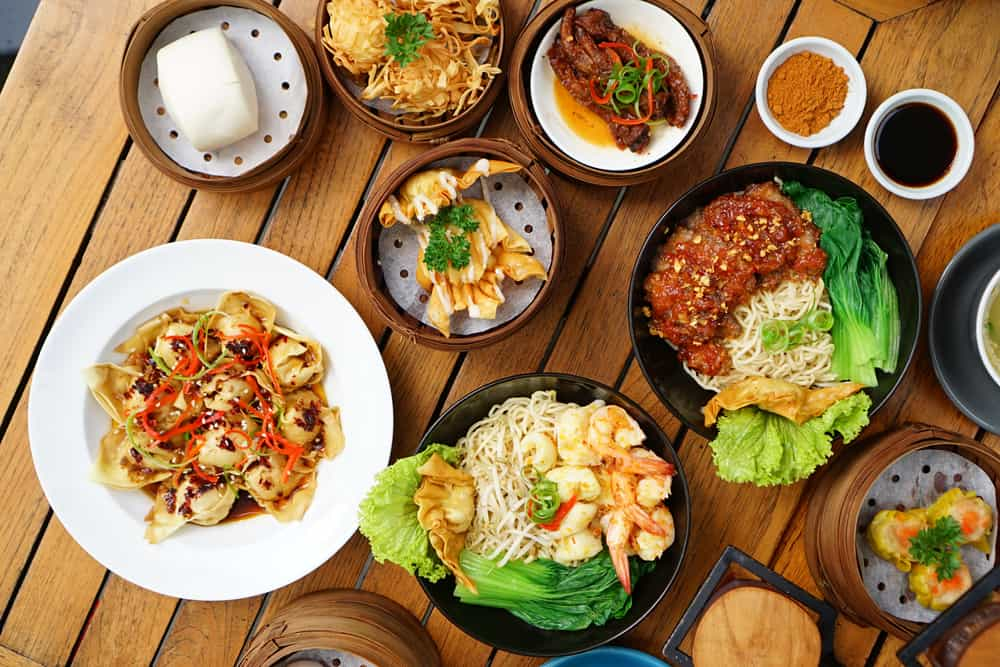 Wooden table filled with thai food