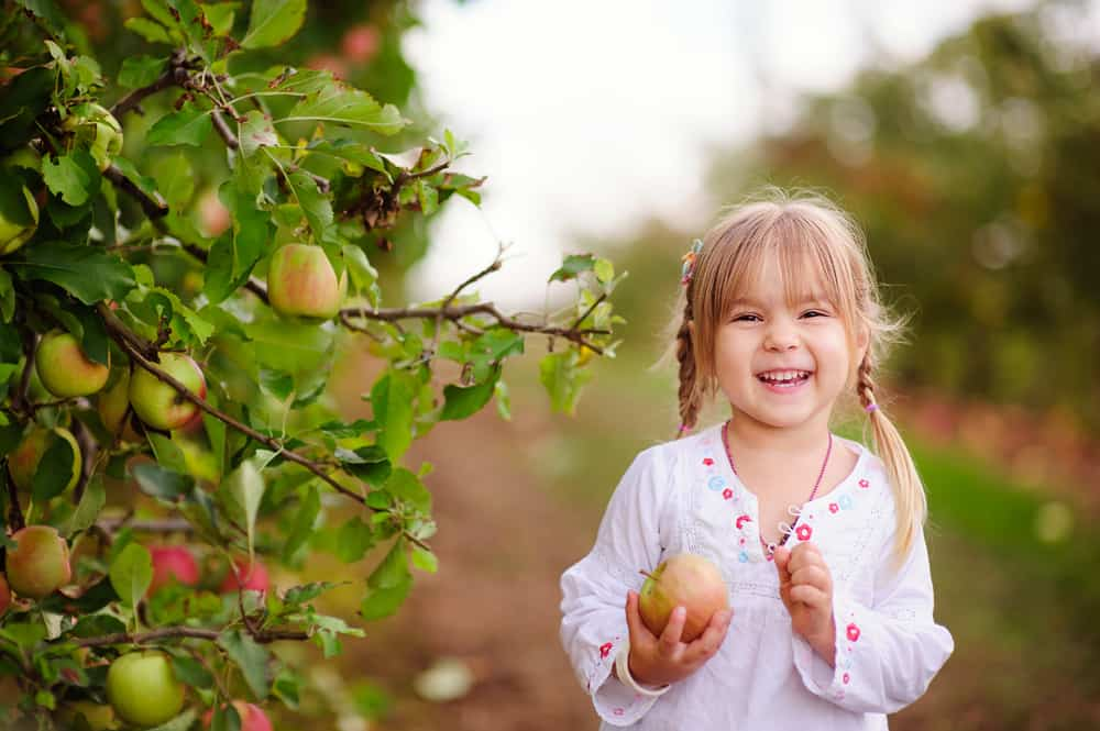 Girl holding an apple and smiling