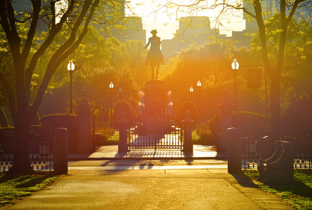 a colorful, hazy sunrise at boston common with a statue of man on horse