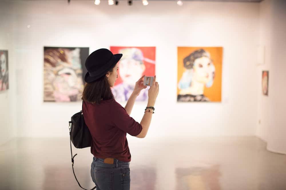 Woman taking photos in a art gallery
