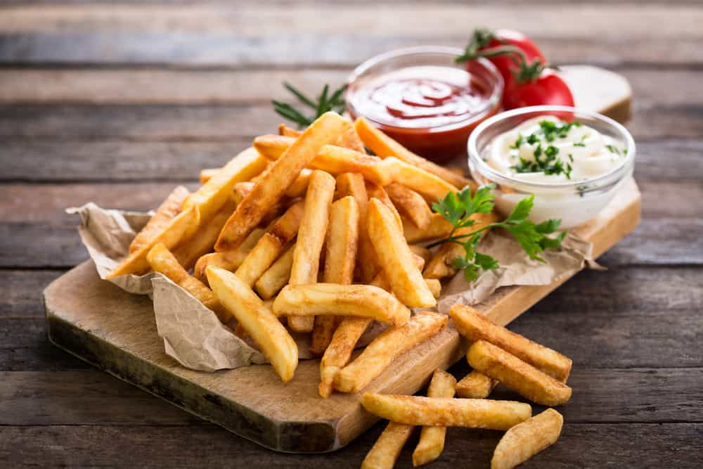 French fries on a slab of wood next to sauces