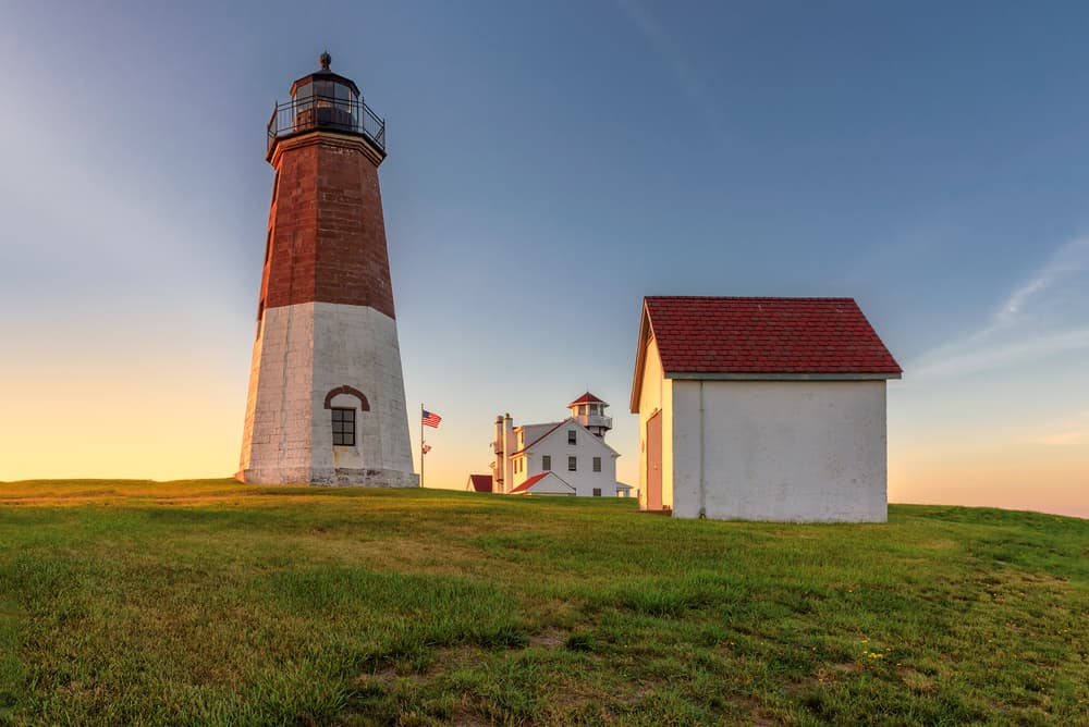 Lighthouse and two small buildings under a blue sky, things to do in Narragansett