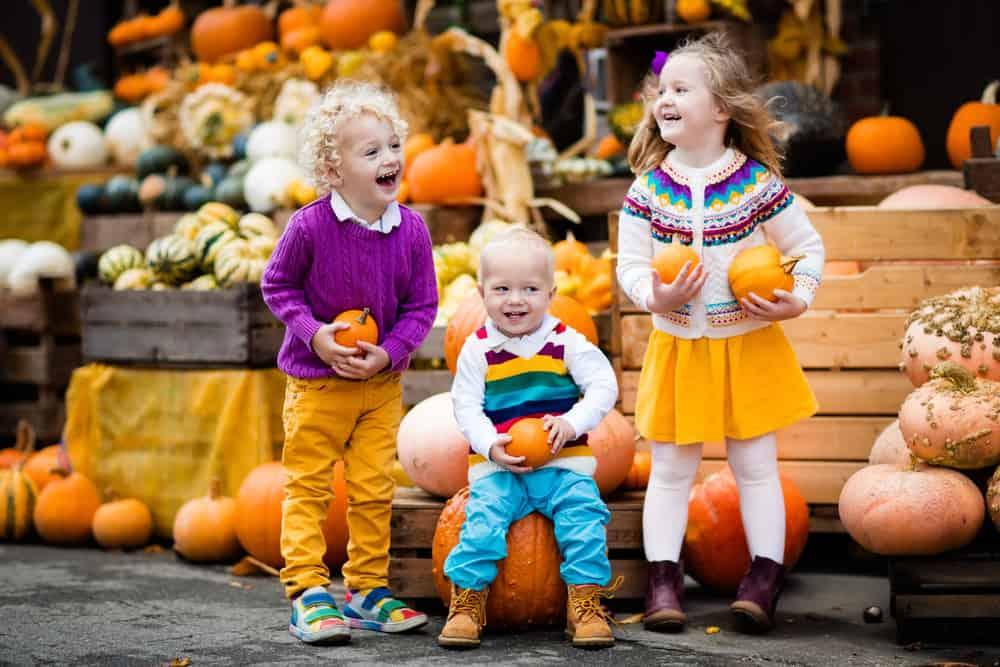 Children sitting next to pumpkins smiling
