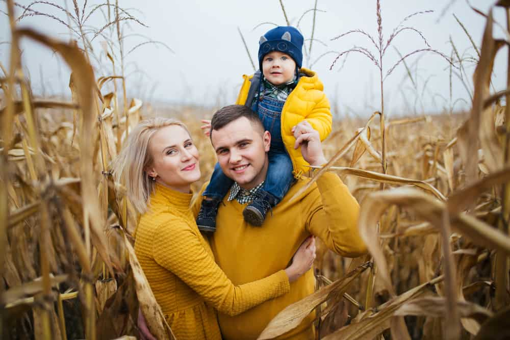 Mother, father, and son smiling in a corn maze