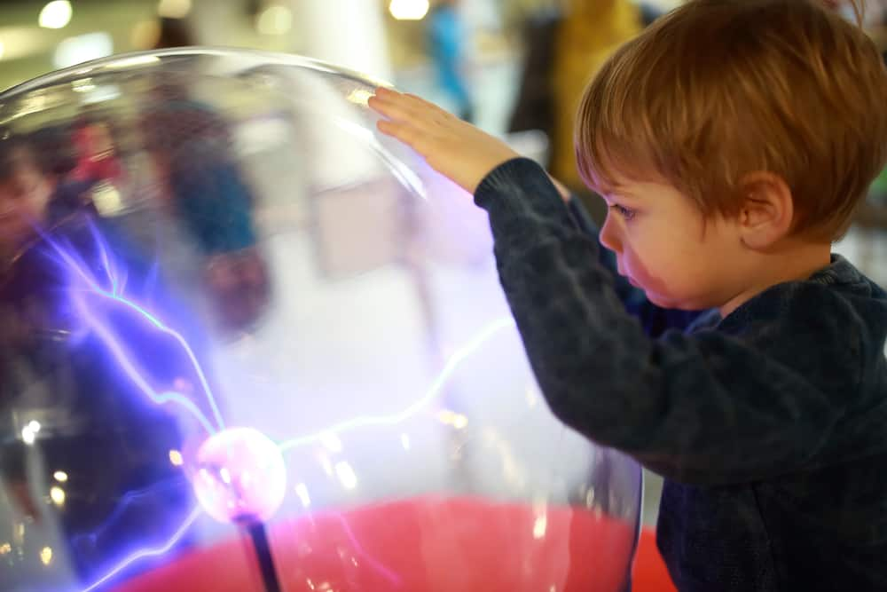 Kid looking into an electricity exhibit