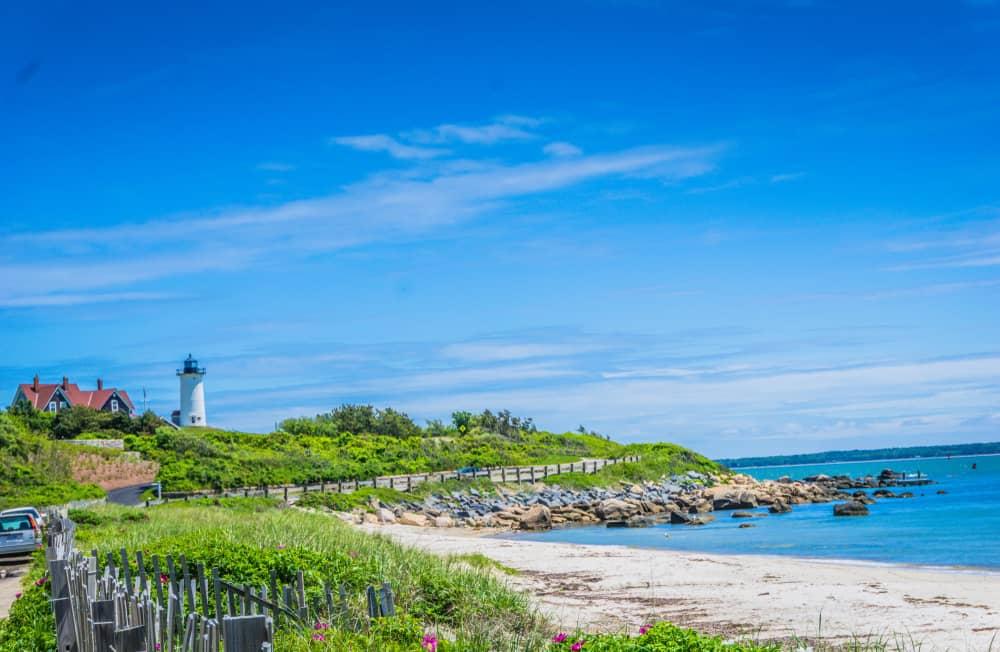 Ocean with sandy beach and a lighthouse
