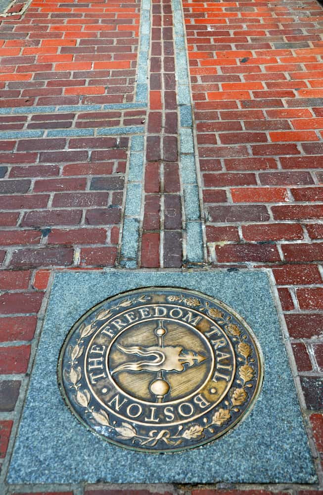 a plaque on a brick sidewalk, the freedom trail in bsoton