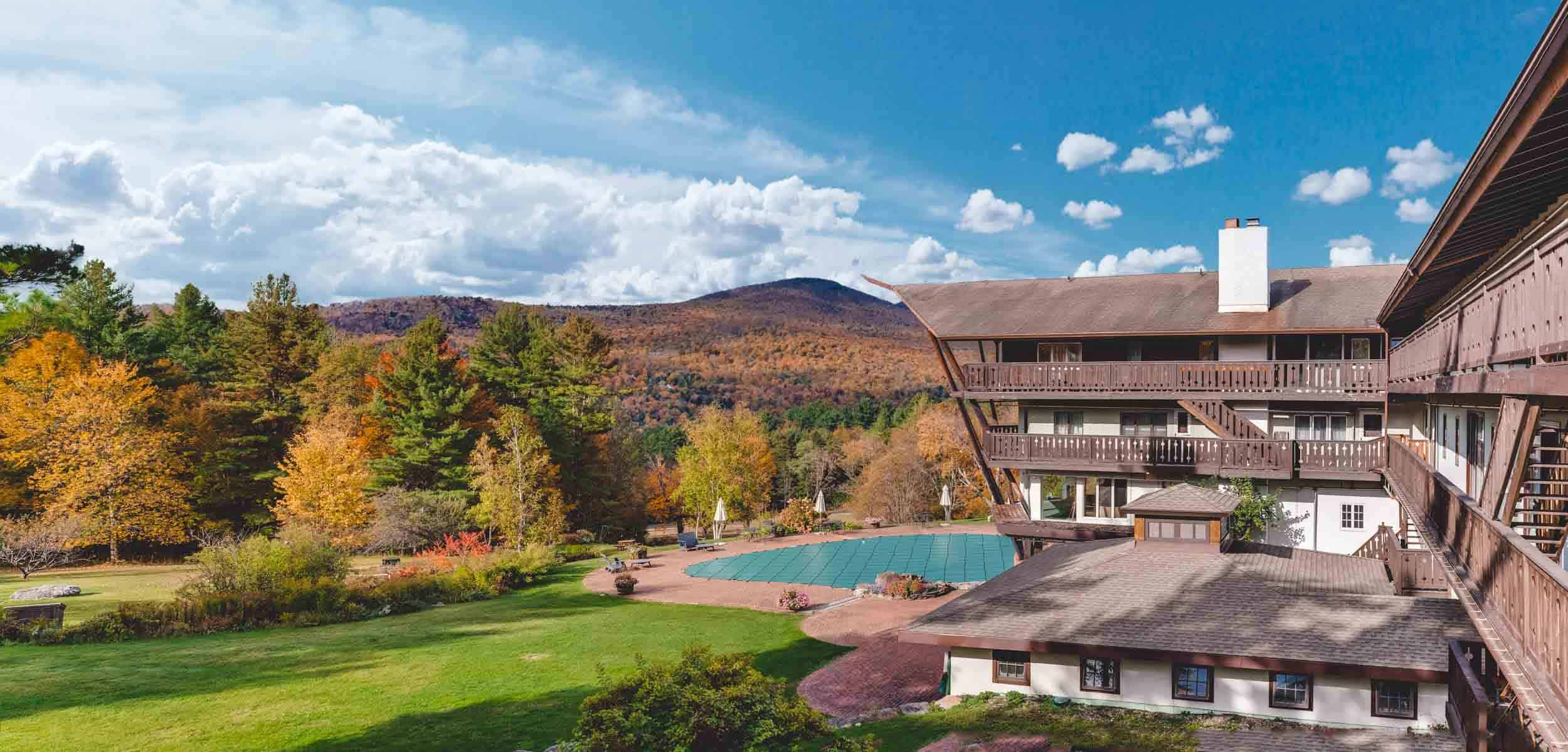 Resort with a pool next to mountains in the fall