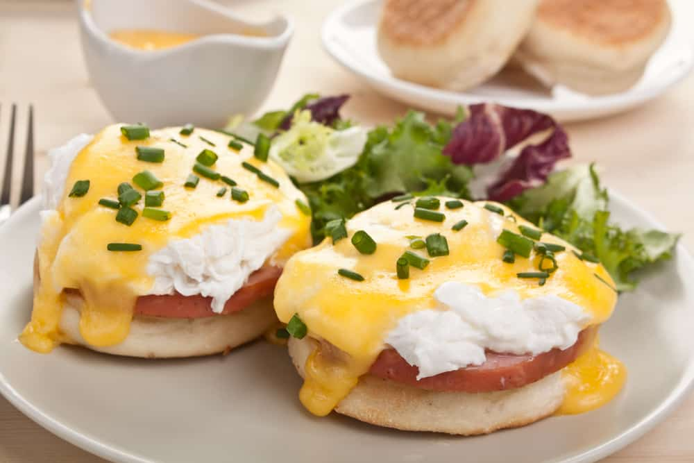 Eggs benedict on a plate with chives