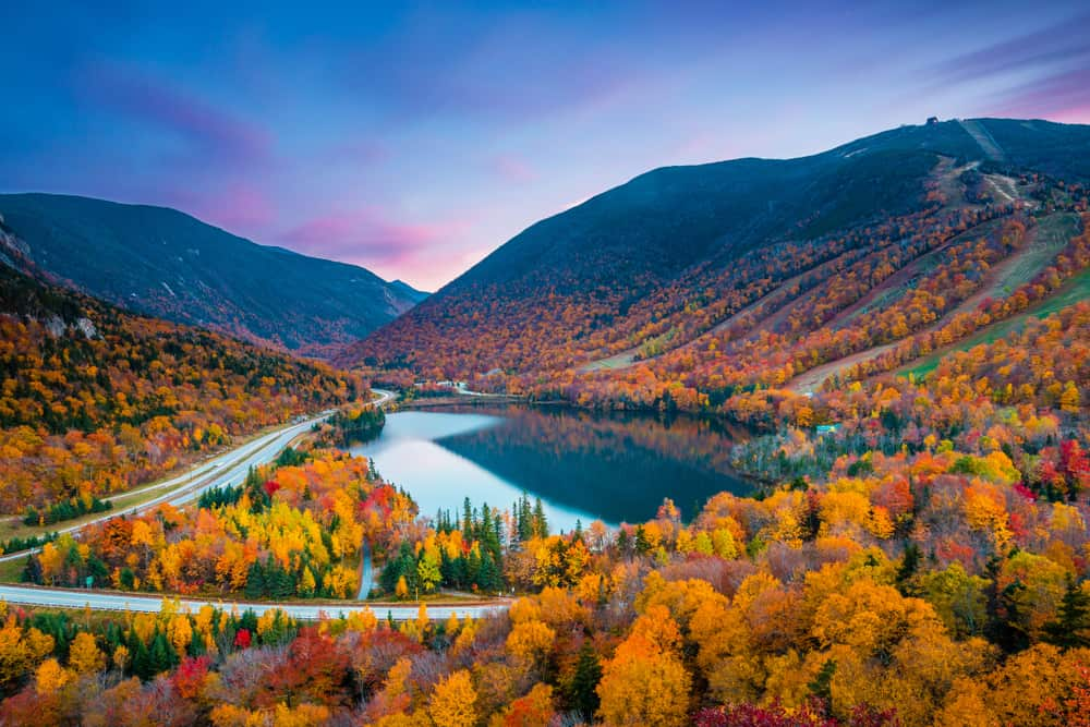 serene lake surrounded by fall foliage mountains and a purple sky