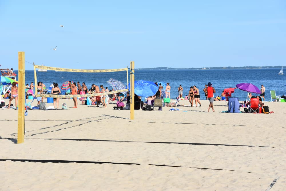 Beach volleyball court on the sandy beach with tons of people hanging out