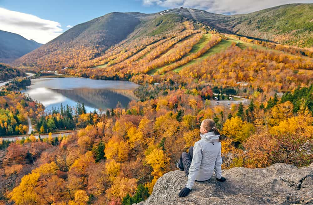 Woman on a rock looking at mountains in the fall, fall foliage in new hampshire
