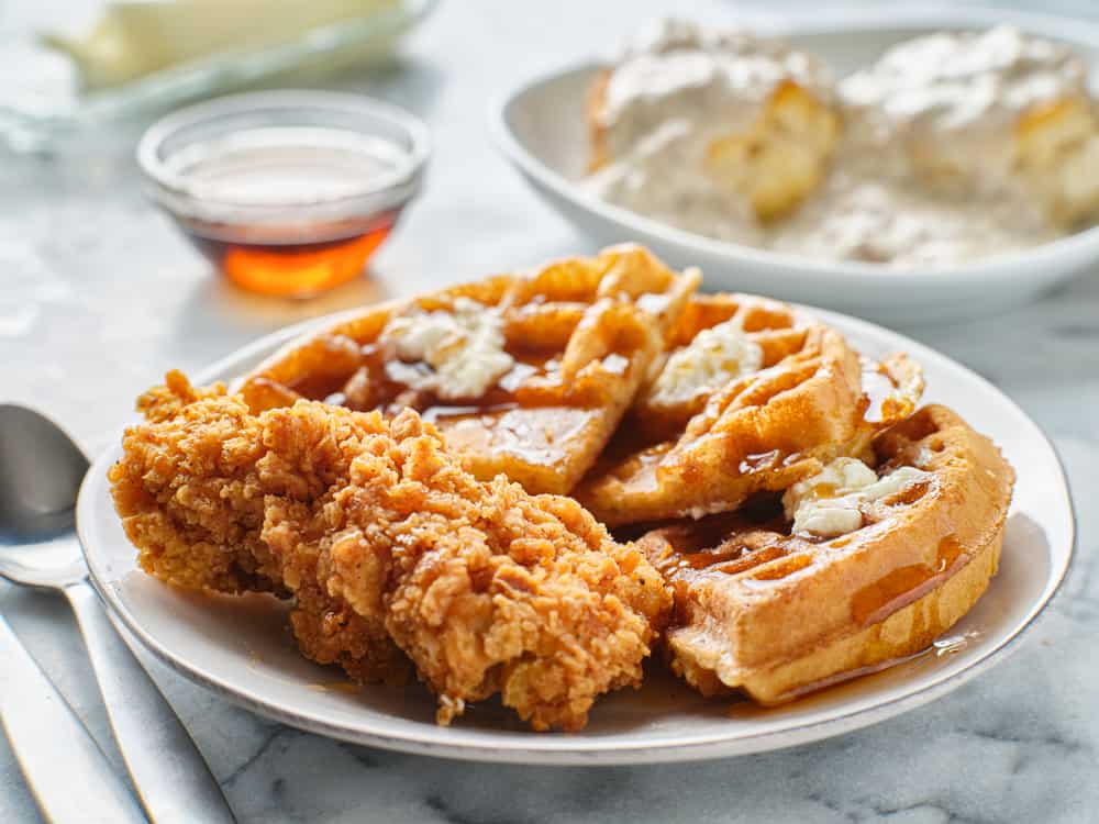 Chicken and waffles with maple syrup on a plate