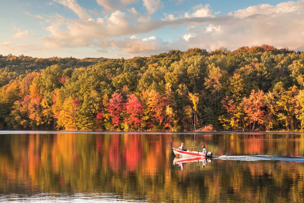 Person kayaking on the lake in the fall