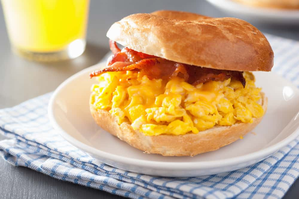 Bagel sandwich with eggs and bacon on a plate