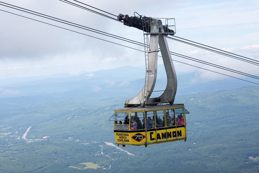 Yellow cable car carrying people up a mountain