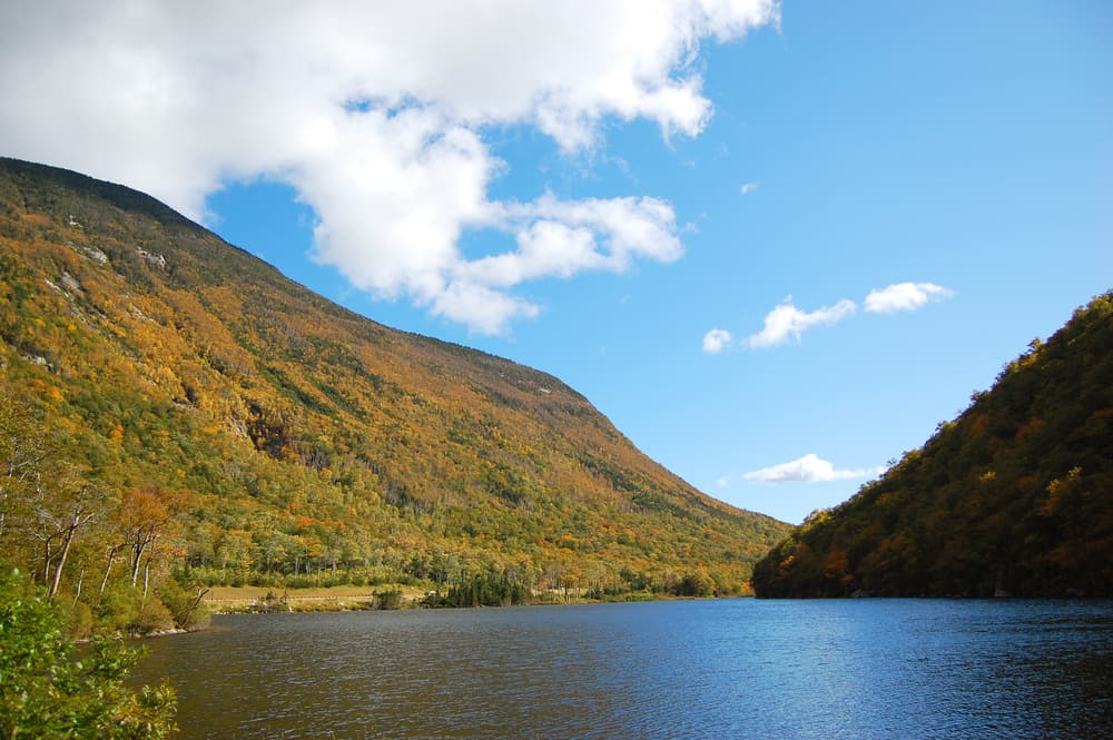 Peaceful lake under a blue sky next to a mountain
